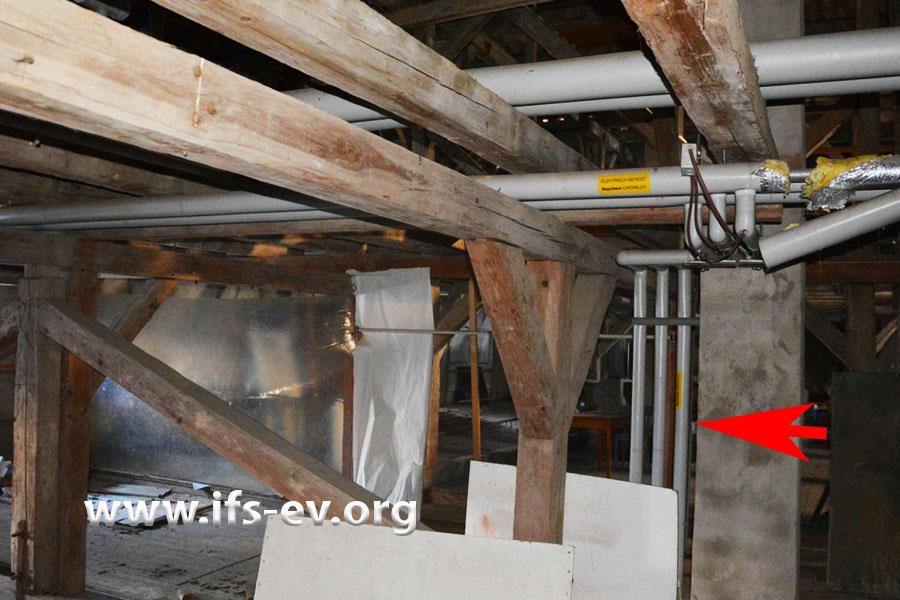 Die Hauptleitungen verlaufen durch das unbeheizte Dachgeschoss. Von dort zweigen Leitungen zu den Wohnungen ab; das Bild zeigt beispielhaft einen solchen Abzweig (Pfeil).