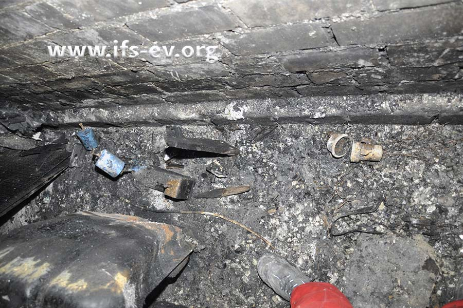 Auf dem Boden der Arbeitsgrube liegen der Fahrzeugtank, Reste einer Palette und Werkzeuge.