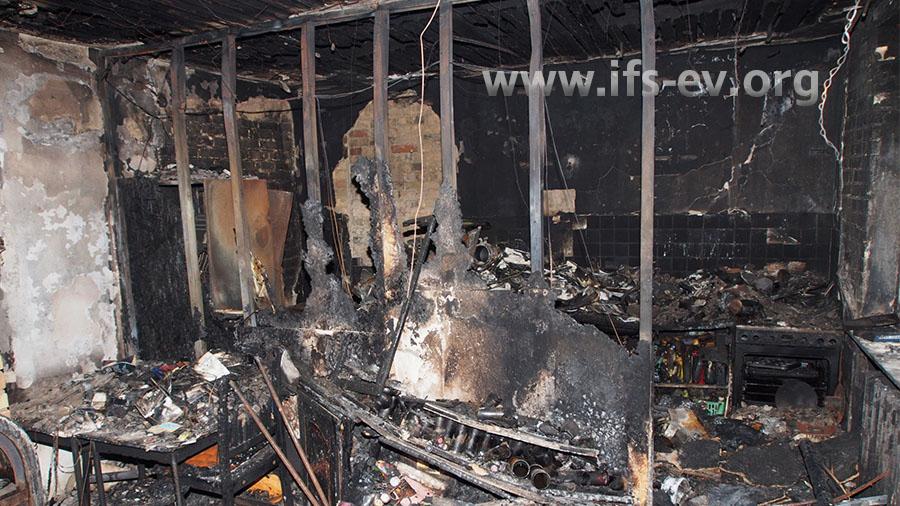 Ein Blick vom Wohnzimmer in Richtung der Küche. Die Leichtbauwand ist bis auf die Metallständer  verbrannt.