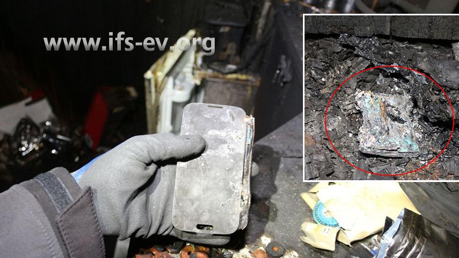 Das Telefon ist relativ gut erhalten; der Akku wird getrennt davon im Brandschutt gefunden (kleines Bild).