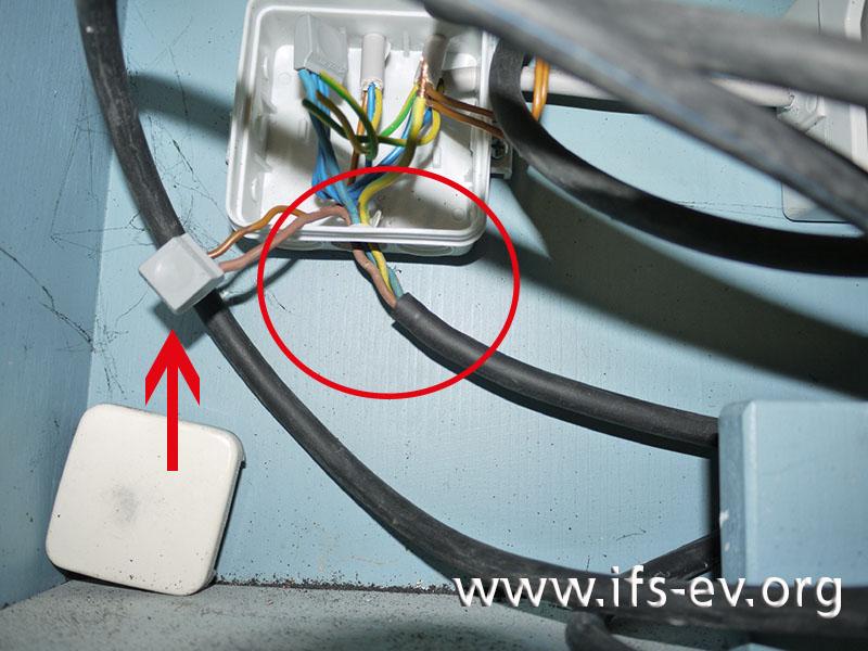 Geöffnete Verteilerdose mit Verbindungsdosenklemmen: Die fehlende Zugentlastung des Anschlusskabels ist markiert; der Pfeil zeigt auf eine Verbindungsdosenklemme.