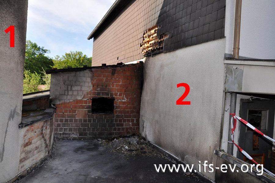 Blick über das Garagendach zwischen dem betroffenen Haus (1) und dem Nachbarhaus (2). Das Feuer ist vor der Wand zum Spitzboden des Anbaus entstanden, die in der Bildmitte zu sehen ist.