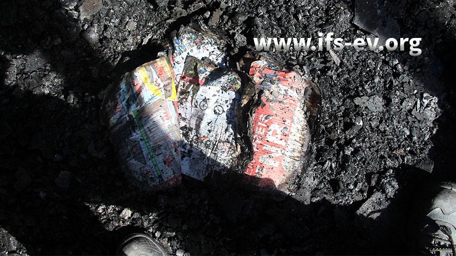 Reste verbrannter Zeitungen im Brandschutt