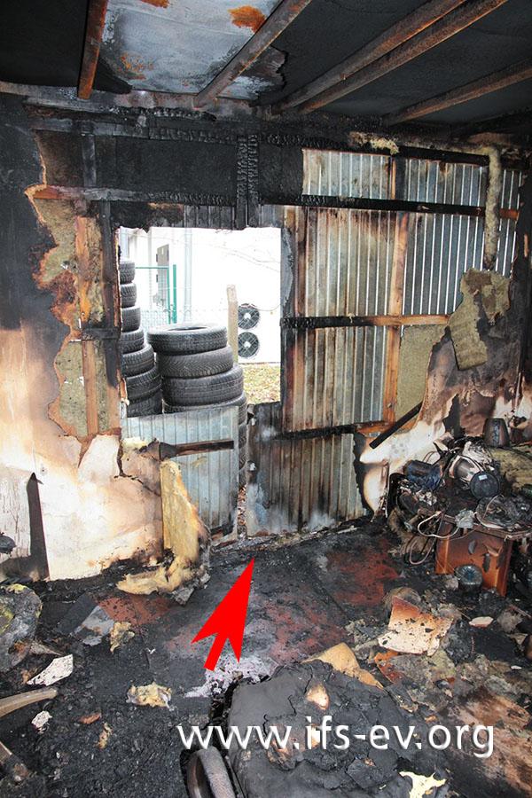 Der Schadenschwerpunkt innen: Unter dem Fenster gibt es im Fußbodenbereich direkt an der Containerwand stark ausgeprägte Brandschäden (Pfeil).