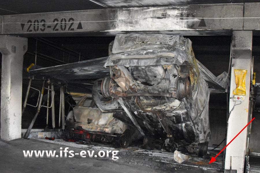 Die untere Bühne des Duplexparkers wurde angehoben; ursprünglich steckte der ausgebrannte Wagen in der unteren Ebene (Pfeil).
