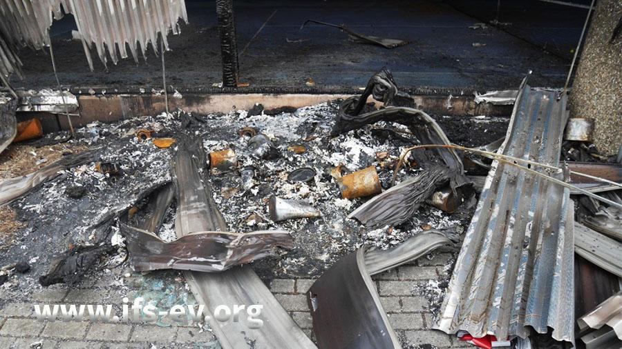 Im Brandschwerpunkt sind noch Abfälle zu sehen; die Müllcontainer sind fast vollständig verbrannt.
