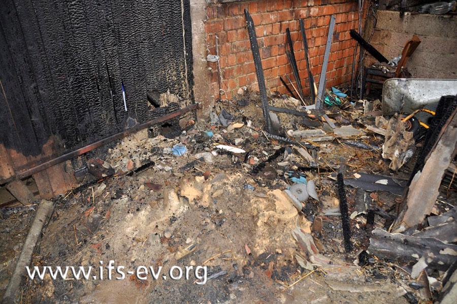 Von außen sind die Brandzehrungen am Tor hingegen nicht zu übersehen und reichen bis zum Erdboden hinab. Davor liegen Reste des Abfallsackes im Brandschutt.