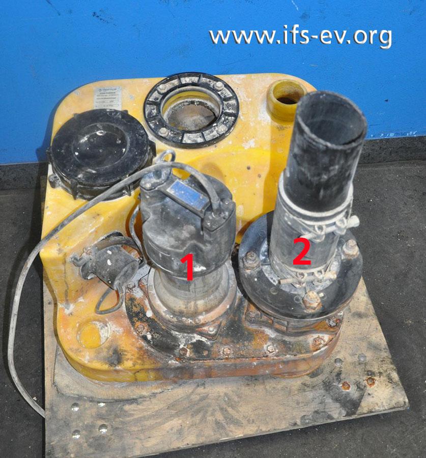 Die Anlage besteht unter anderem aus dem gelben Sammelbehälter sowie aus der Pumpe (1) und der Rückschlagklappe (2), die auf einer Guss-Gehäuseplatte montiert sind.