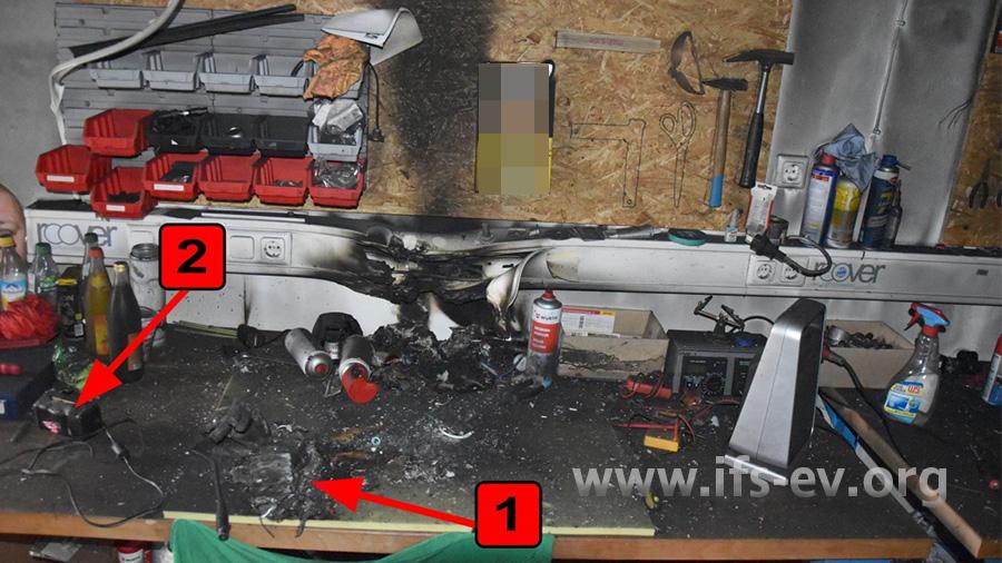 Ein zweiter Schadenschwerpunkt befindet sich auf der Werkbank: Hier liegt ein weitgehend zerstörter Lithium-Ionen-Akku (1) mit dem zugehörigen Ladegerät (2), das zum Schadenzeitpunkt eingesteckt war.