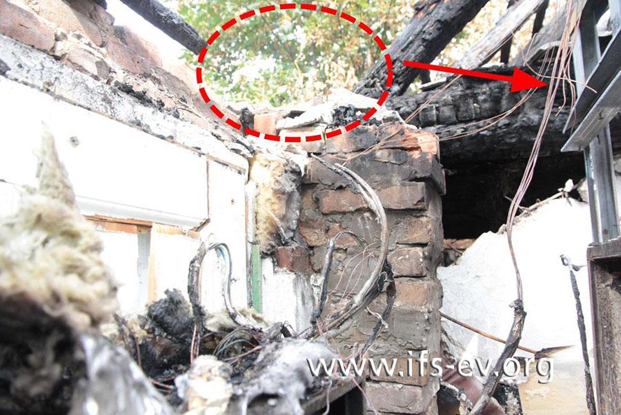 Sicht von innen auf den Brandschwerpunkt: An der Herdleitung, die dort vor dem Feuer verlief, gibt es Kurzschlussspuren (Pfeil).