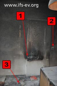 Der Brandraum: An der Tür gibt es eine auffällige Brandsprur (1). Pfeil 2 markiert die Steckdosen und Pfeil 3 eine Packung Wunderkerzen.