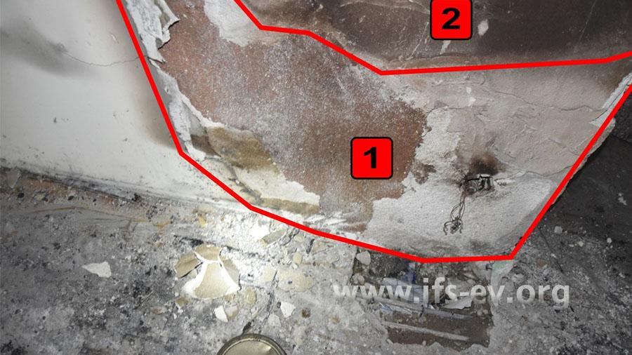 An der Wand ist die Tapete verbrannt (1) und darüber ist der Putz abgeplatzt (2). Direkt hiervor soll der Rollwagen gestanden haben.