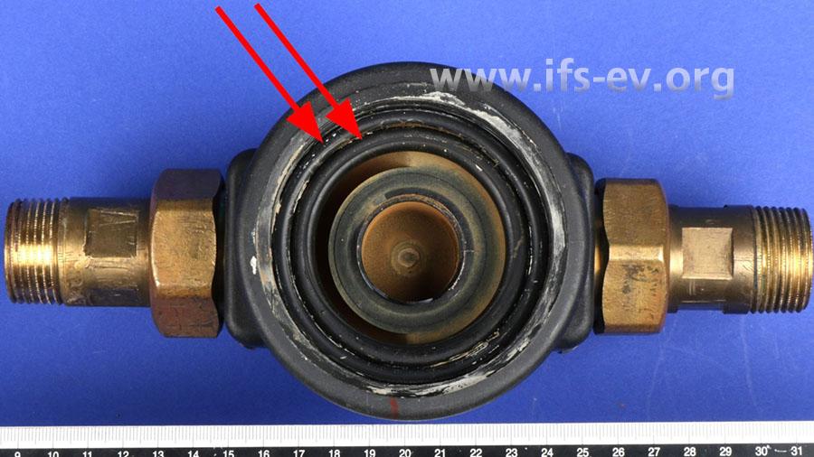 Nach dem Demontieren der Sichtglocke zeigen sich Reste von Schmierpaste im Dichtungsbereich zwischen Gehäuse und Glocke (weißer Belag). Außerdem liegen zwei O-Ringdichtungen vor (Pfeile).