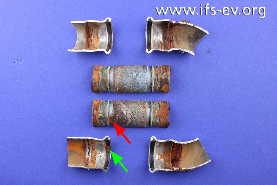Das Rohrstück und die Pressverbindungen werden aufgetrennt. Dabei fällt eine runde, bräunliche Verfärbung auf (Pfeile).