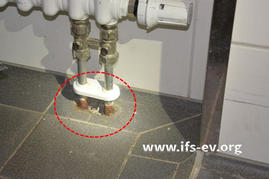 Der Heizkörperanschluss in einem weiteren Raum: Unter der Kunststoffrosette ist Korrosion an den Rohren zu erkennen. Eine Abdichtung ist nicht vorhanden.