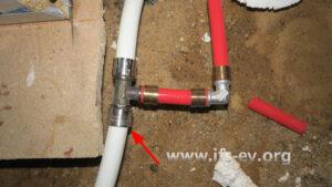 Die Schiebehülsenverbindung im eingebauten Zustand: In das weiße Bestandsrohr wurde ein T-Stück eingesetzt und ein rotes Heizungsrohr angeschlossen. An der mit dem Pfeil markierten Verbindung trat  Wasser aus.