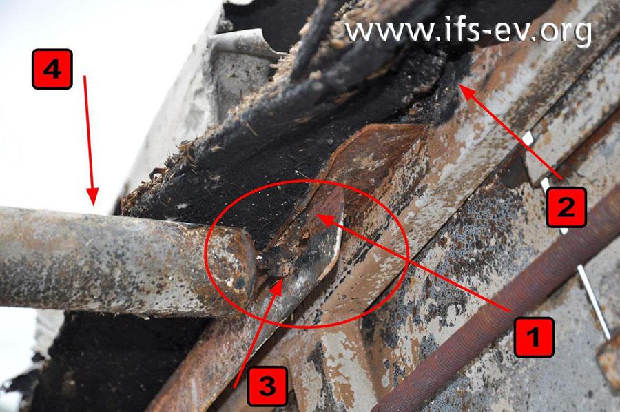 Die Tragerolle (4): Angrenzend an die innenseitige Mutter (3) ist oberhalb des Befestigungsschlitzes ein langer Riss (1) in der Befestigungsschiene zu erkennen. Die Schiene zeigt in diesem Bereich deutliche Anlauffarben (rote Ellipse). An der Gummiabgrenzung gibt es eine Durchbrennung (2).