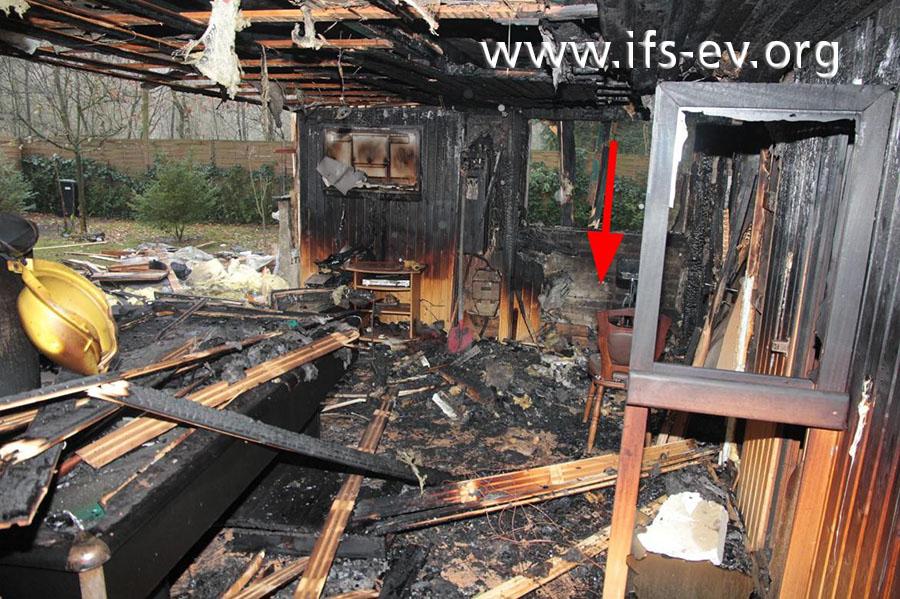 Vor dem Fenster reichen die Brandzehrungen bis auf den Boden (Pfeil).