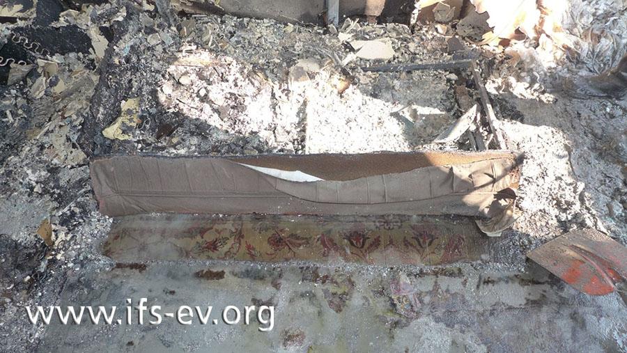 Der Gutachter hat die Frontblende des Sofas wieder aufgestellt. Sie war in der frühen Brandphase umgekippt und ist darum auf der Vorderseite noch gut erhalten.