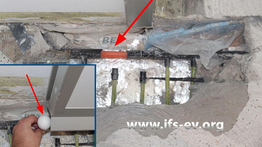 An der Leckagestelle wurde der undichte Abschnitt herausgetrennt und die Lücke mit dem orangefarbenen Kunststoffrohr überbrückt. Das kleine Bild zeigt den Türstopper, der über dieser Stelle platziert war.