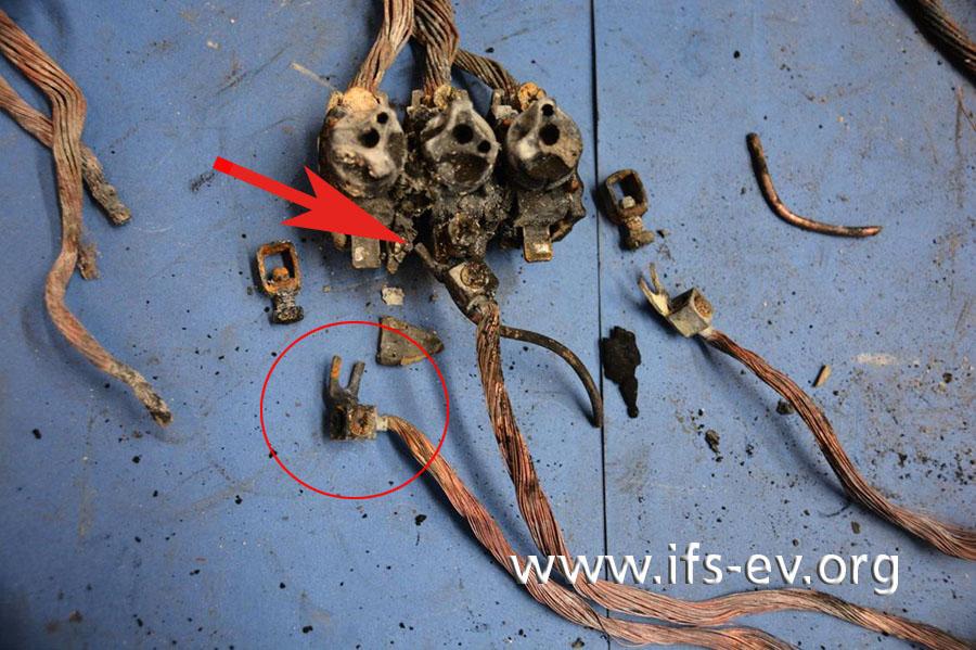 Großaufnahme des Neozed-Elements, an das die Außenleiter der Einspeiseleitung angeschlossen waren; ein Gabelkabelschuh (Kreis) kann hier nur über einen Zinken der Gabel angeschlossen werden (Pfeil).
