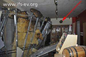 Die Trockenbauwände der Brennerei wurden in die Probierstube gedrückt. Dort gibt es oberflächliche Brandspuren, z. B. an einem Gesteck an der Wand (Pfeil).