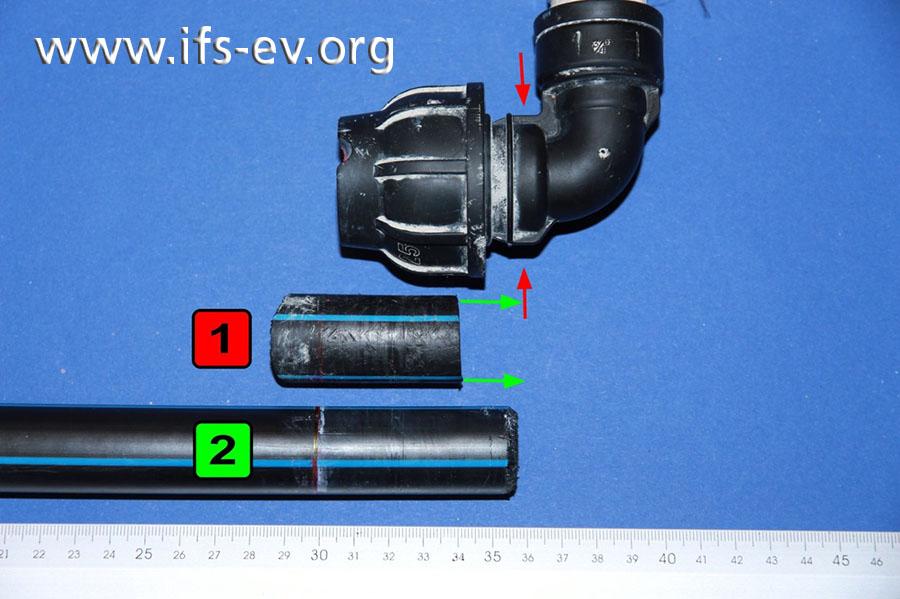 Das Rohr (1) war nicht bis zum Anschlag (rote Pfeile) in das Fitting eingesteckt. An einem Vergleichsrohrstück (2) ist die Abweichung der Einstecktiefe deutlich zu erkennen.