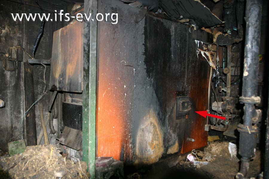 Der Festbrennstoffkessel im Heizungsraum: In der rechten Seitenwand befindet sich eine Explosionsklappe (Pfeil).