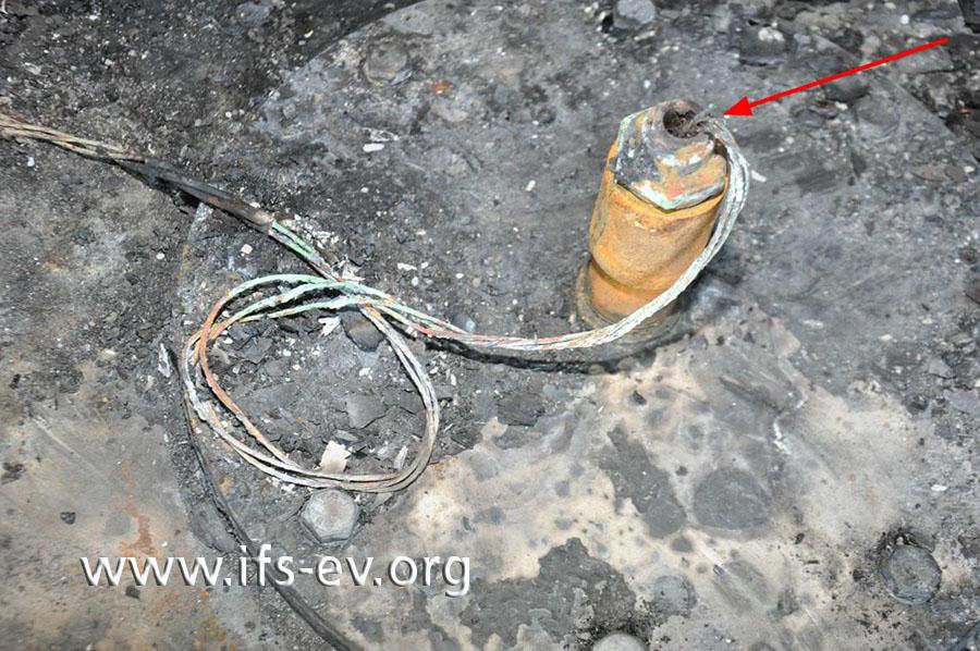 Auf dem Tankdeckel befindet sich die Einführhülse der Tankheizung. Im Bereich der Durchführung ist die Leitung der Tankheizung freigebrannt und einzelne Litzen sind durchtrennt (Pfeil).