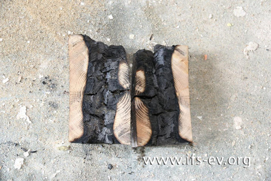 Am aufgetrennten Balken sind intensive Brandzehrungen durch das ganze Bohrloch zu sehen.
