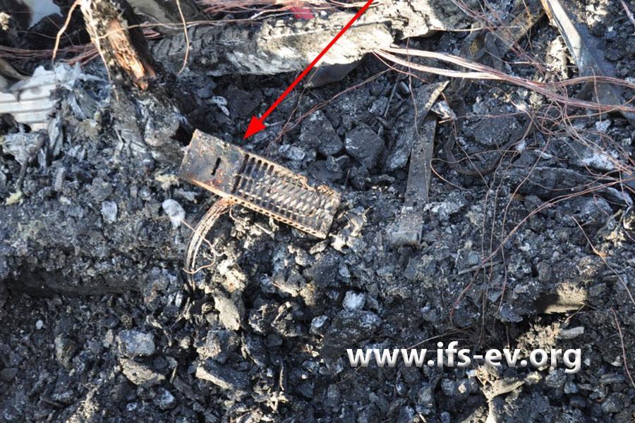 Im Brandschutt liegen die Reste eines Heizgerätes.