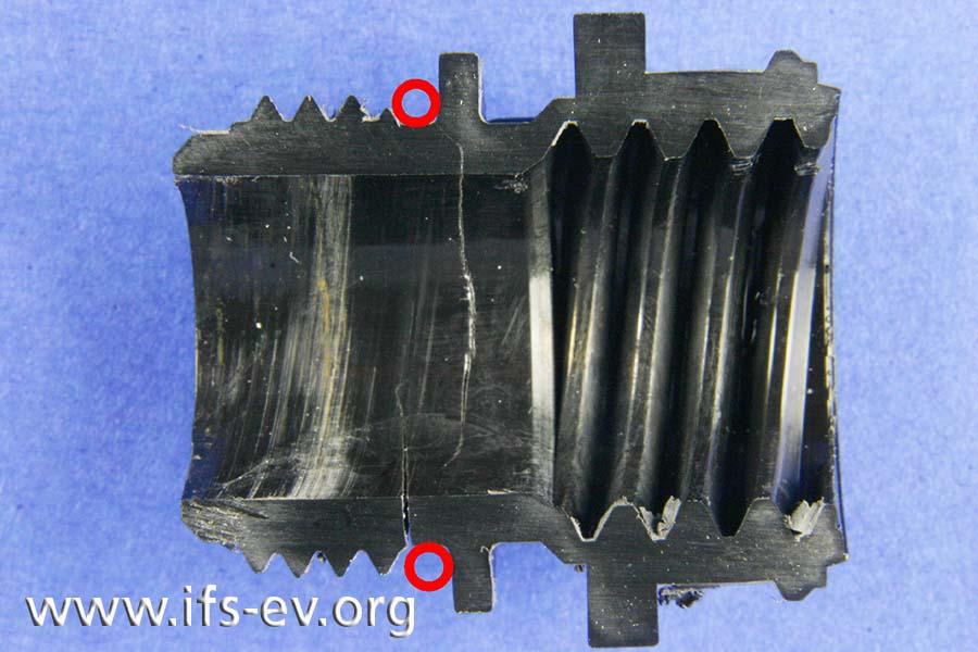 Längsschnitt durch das Bauteil: Vom Bereich der Nut gehen mehrere Rissbildungen aus. Die Markierungen zeigen die ehemalige Position des O-Ringes.