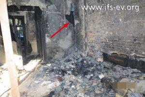 Das Wohnzimmer: Rechts hat das Sofa gestanden; die Wand zum Flur ist eingedrückt (Pfeil).