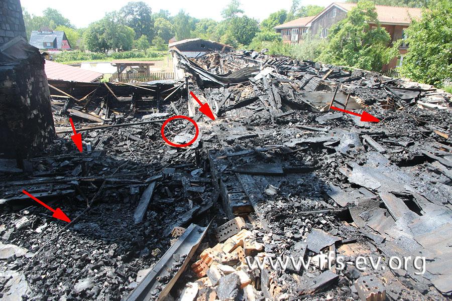 Im Brandschutt auf dem Dachboden liegen elektrische Zuleitungen (Pfeile). Nahe dem Schornstein gibt es an einer davon Kurzschlussspuren (Kreis).