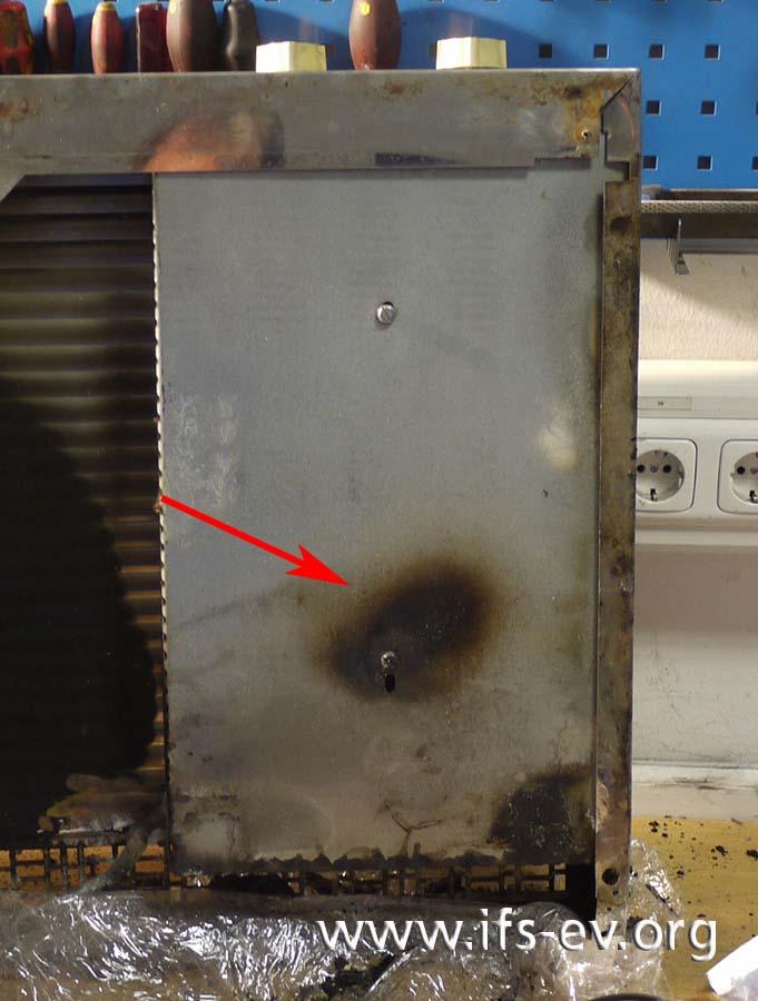 An der Abdeckplatte auf der Unterseite des Herdes ist im Bereich der hinteren Herdplatte eine thermische Beschädigung zu sehen.