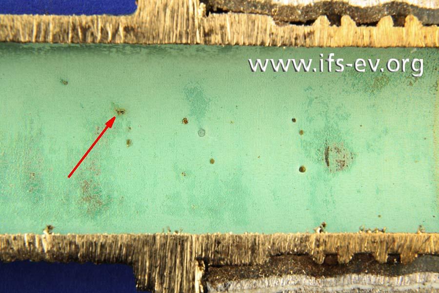 Die Innenwand des aufgetrennten Fittings: Der Pfeil markiert die Leckagestelle.