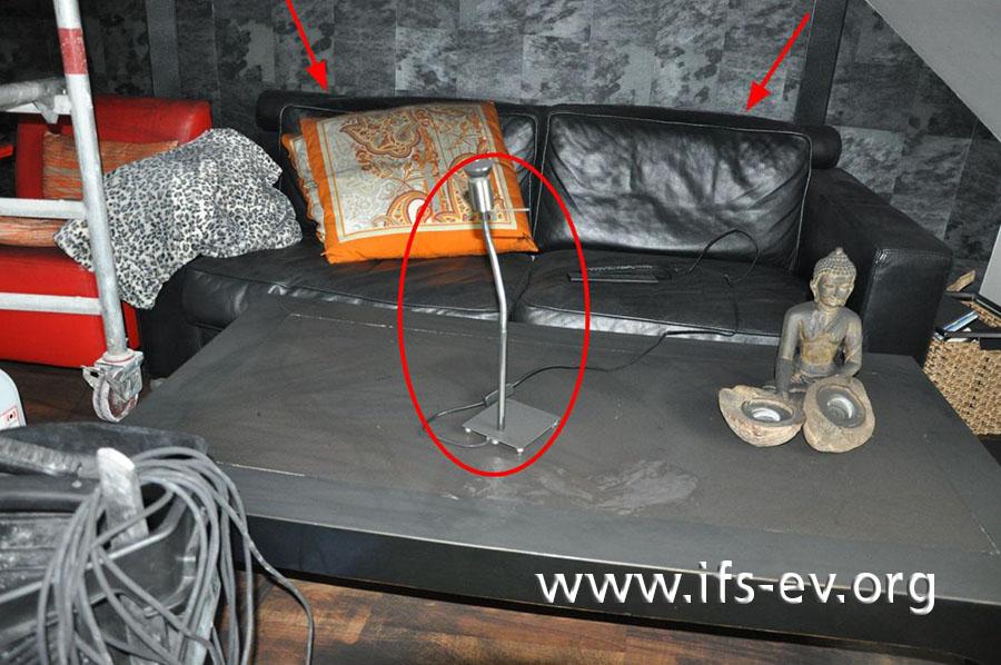 Auch in der Nachbarwohnung standen zwei Lampen hinter dem Sofa (Pfeile). Eine davon asserviert der Gutachter für eine Laboruntersuchung.