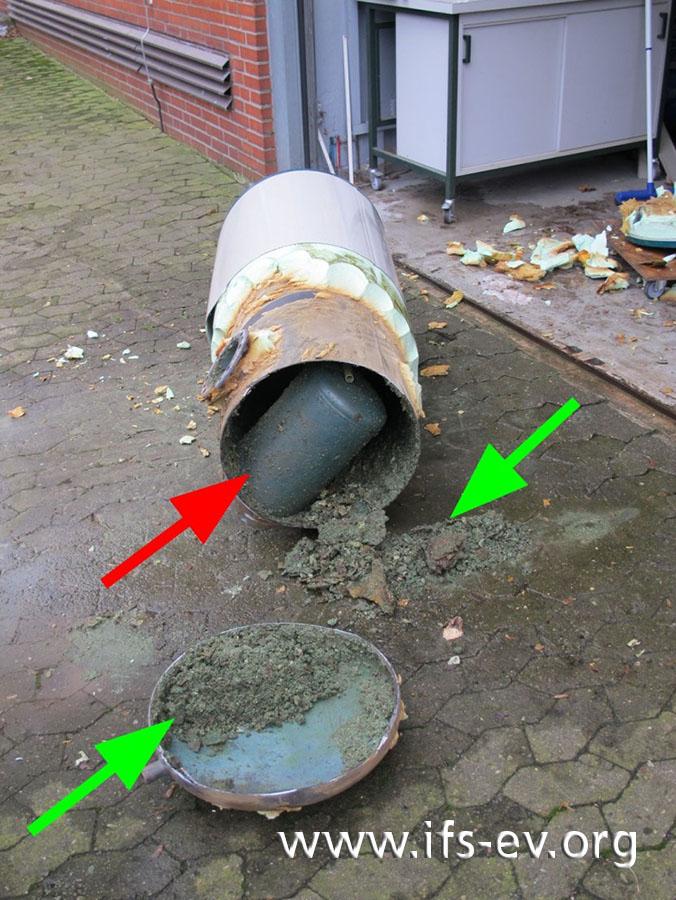 Der Speicher wird aufgeflext: Im Inneren ist die Brennkammer zu sehen (roter Pfeil), und es sind ausgeprägte Korrosionsprodukte und Kalkabscheidungen vorhanden (grüne Pfeile).