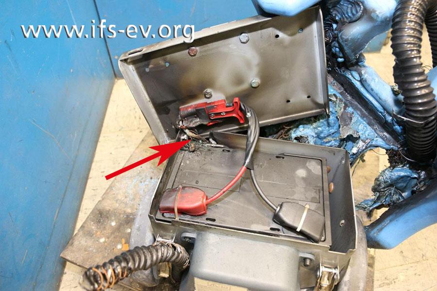 Im geöffneten Batteriefach ist zu sehen, dass Plus- und Massekabel durch eine Aussparung geführt werden.