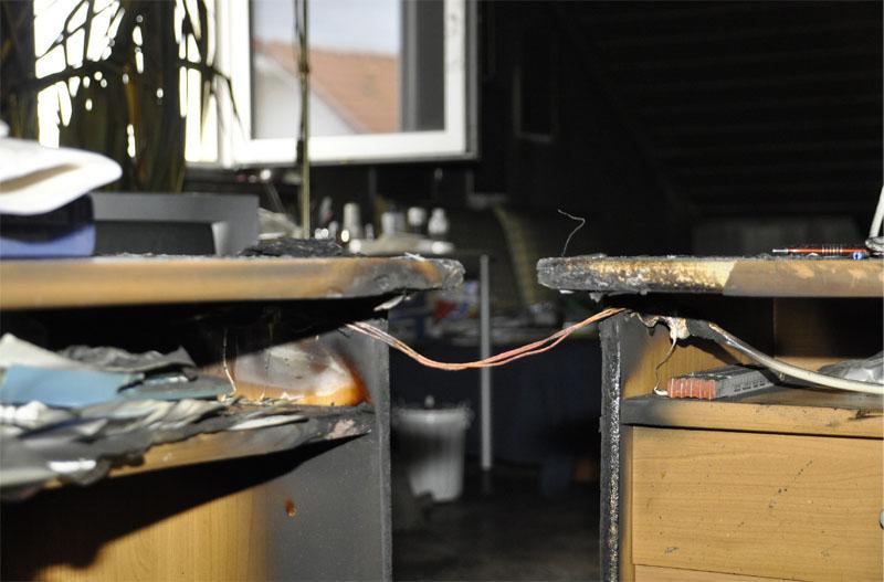 Die Isolation der Verlängerungsleitung ist zwischen den beiden Schreibtischen verbrannt.