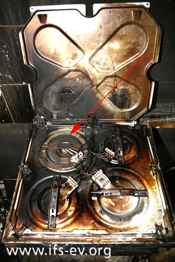 Bei hochgeklappter Abdeckung auf der Unterseite der Kochmulde zeigt sich eine helle Stelle im Bereich der hinteren linken Kochplatte.