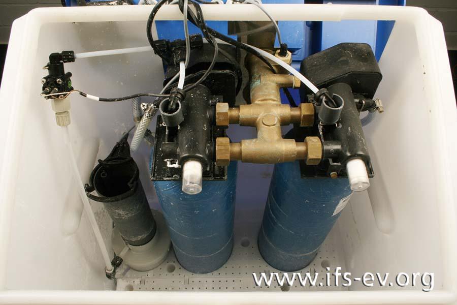 Im Anlagenbehälter befinden sich zwei blaue Austauscherpatronen und die darüber angeordnete Steuereinheit.