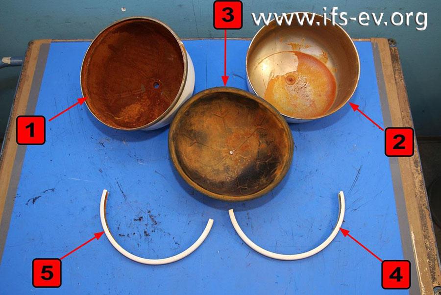 Das Gefäß wird im IFS-Labor untersucht. Es besteht aus den beiden metallenen Halbschalen (1, 2) und zwei halbkreisförmigen U-Bügeln (4, 5) zu deren Fixierung sowie einer Polymerhalbmembran (3), die sich zwischen den Halbschalen befunden hat.