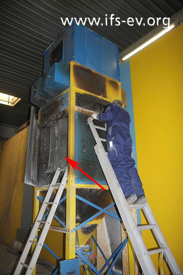 Die Filteranlage: Durch die geöffnete Tür der Hauptfilterkammer sieht man intensive Brandschäden (Pfeil).