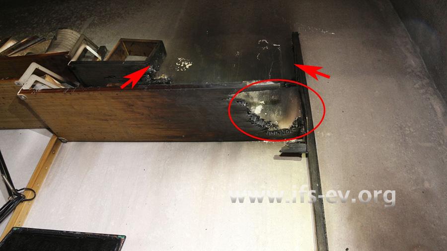 Am unteren Regalbrett gibt es eine Durchbrennung (Ellipse); das obere Regalbrett ist zwischen den Pfeilen komplett verbrannt.