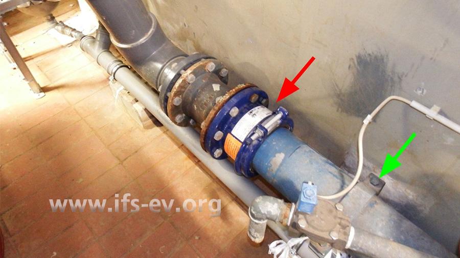 Einbausituation am Schadenort mit der Kupplung (roter Pfeil): Die starre Edelstahl-Rohrleitung ist in Fließrichtung vor der Kupplung mit einer Rohrschelle gut befestigt (grüner Pfeil).