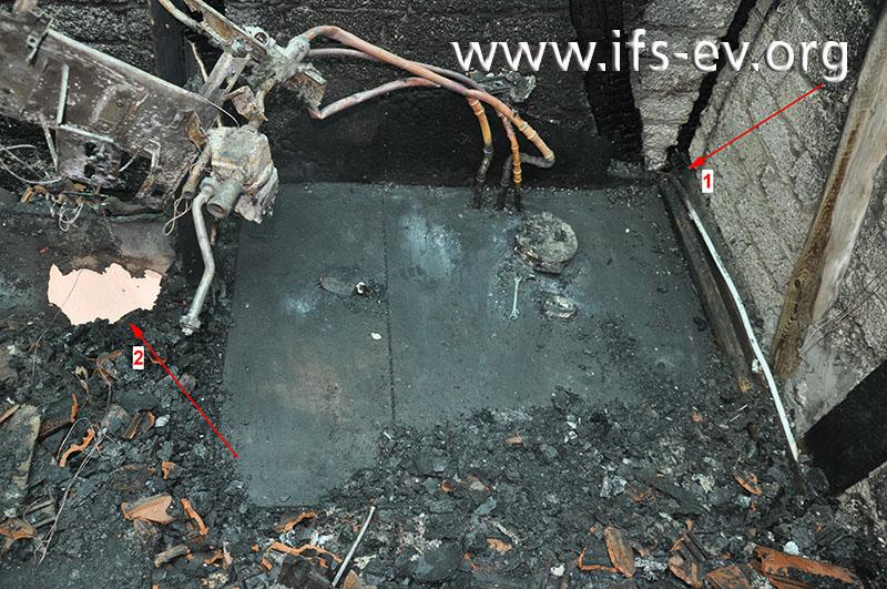 Im geräumten Brandausbruchsbereich verläuft entlang der Außenmauer am Boden eine elektrische Leitung, die im Bereich der Wanddurchführung von der Isolierung freigebrannt ist (Pfeil 1).