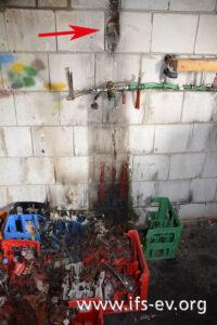 Blick auf den Schadenschwerpunkt mit geschmolzenen Getränkekisten und geschmolzener Steckdose (Pfeil)