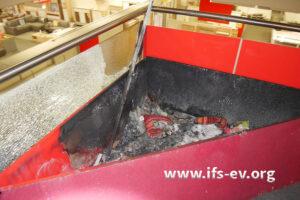 Im Brandschutt in der Kiste sind noch Kissen zu erkennen.
