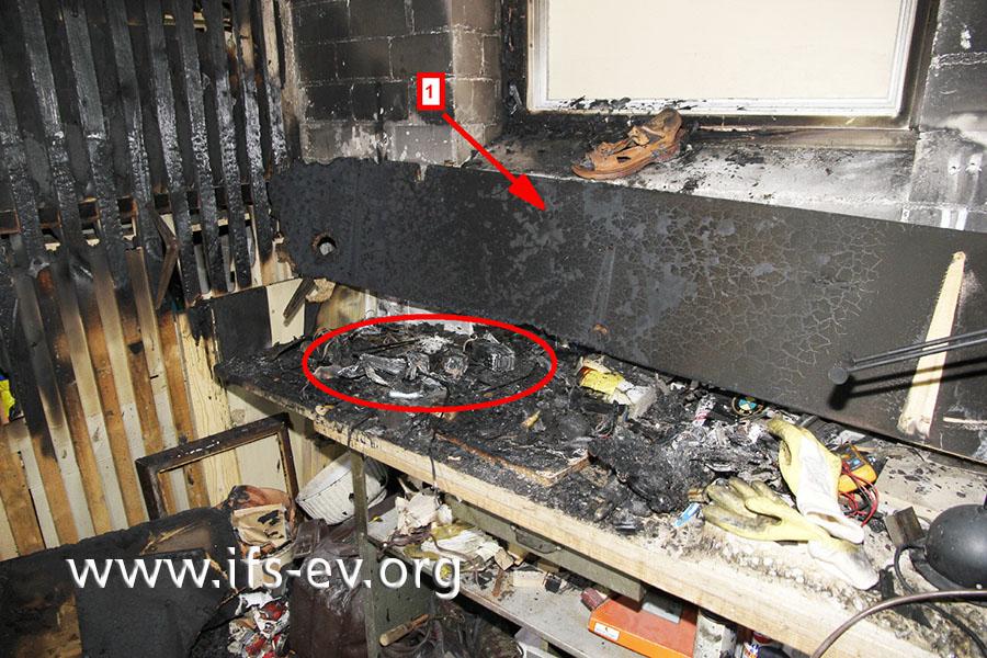 Die Brandzehrungen am Regalbrett (1), das über der Werkbank angebracht war, sind ein Hinweis darauf, wo das Feuer entstanden ist.